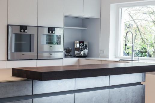 Küche in Farbe Merino und Beton hell gespachtelt mit Gaggenau Backöfen und Bora Kochfeldabzug